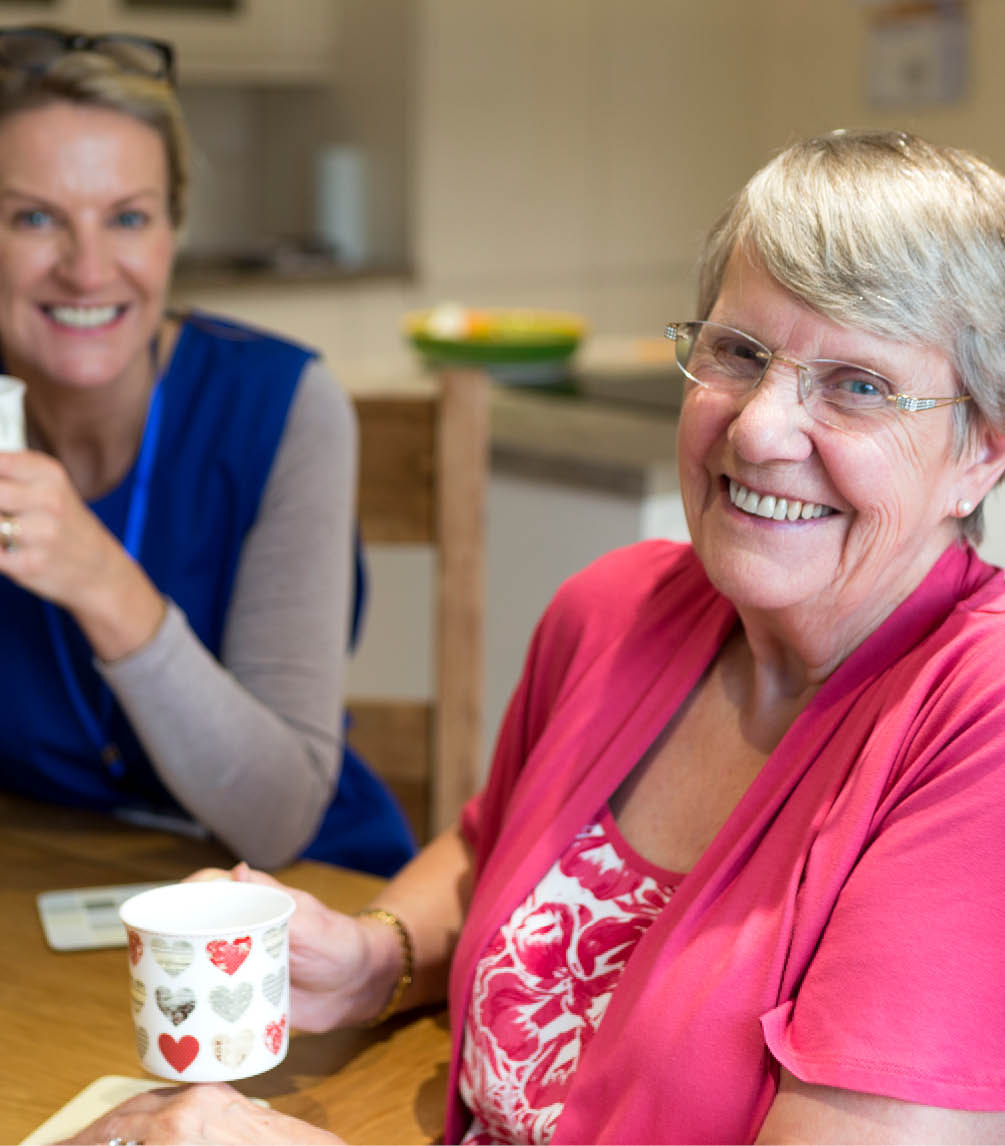 Young woman having a cup of tea with an elderly lady, both smiling