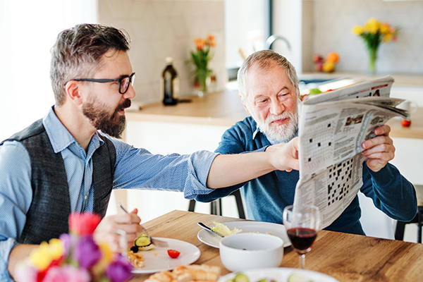 A young man and his father looking at a newspaper together